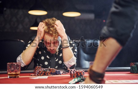 Man sits in casino and feels bad because losing poker game.