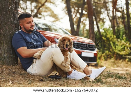 Man sits near the tree with his dog outdoors in the forest.