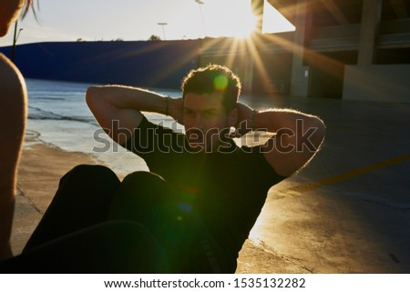 Man sits on a concrete floor with his knees raised and his hands behind his head as he does a sit up #1535132282