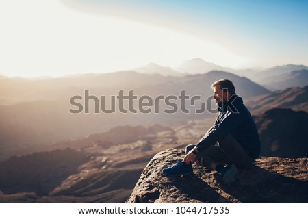 Man sits on edge of cliff on Mount Sinai and looks at sunrise in Egypt. #1044717535