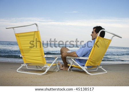 Man sits on the beach alone and looks at an empty chair. Horizontal shot.
