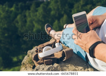 man sits on the ground chating on the phone, sunset #665678851