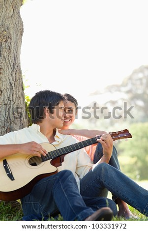 Man sitting against the trunk of a tree while playing a guitar as his friend watches him