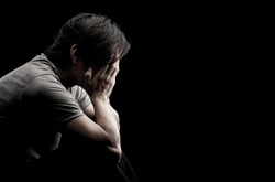 Man sitting alone felling sad worry regret or fear and hand off his face on dark black background