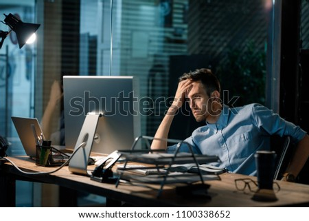 Man sitting alone in office late at night watching computer and solving problem working overhours.