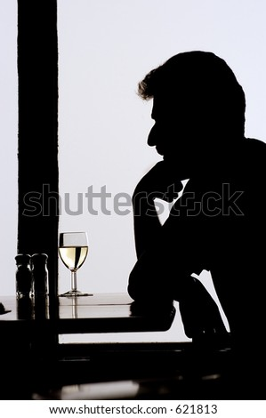 Man sitting alone in the restaurant with a glass of wine