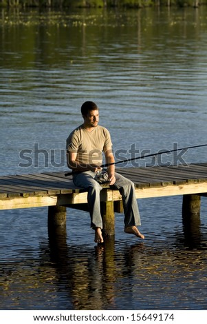 Man sitting alone on a pier fishing in a bay.