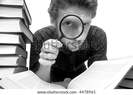 Man sitting amongst books with a magnifier