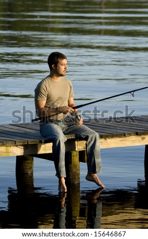 Man sitting and fishing on a dock in a bay as the sun is setting.