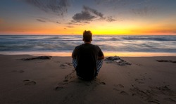 Man sitting and watching sunset over the sea, Sardinia, Italy