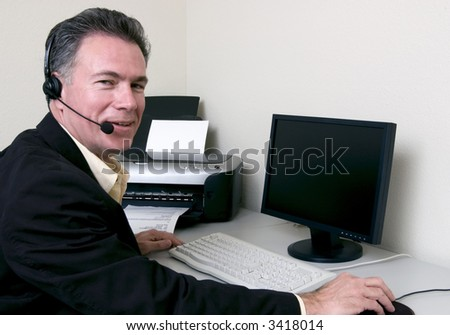 Man sitting at a helpdesk with a happy expression on his face.