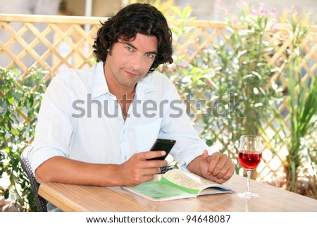 Man sitting at an outdoor cafe table with a cellphone and glass of rose