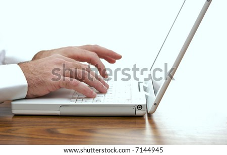 man sitting at desk typing on the keyboard of a white laptop