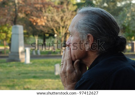 Man sitting at gravesite with a look of sadness. - stock photo