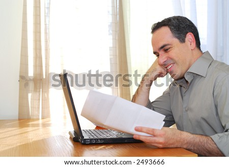Man sitting at his desk with a laptop and papers looking happy