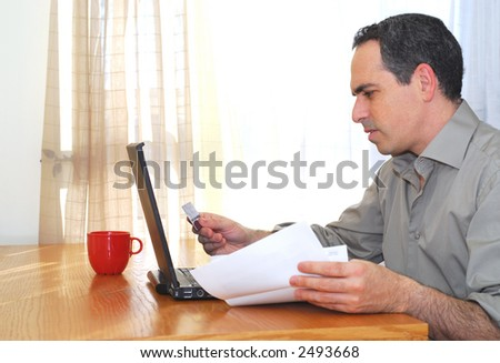 Man sitting at his desk with laptop, papers and credit card - stock photo