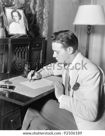 Man sitting at his desk writing a letter with a fountain pen - stock photo