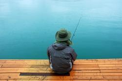 Man sitting at jetty fishing near lake during rainy day