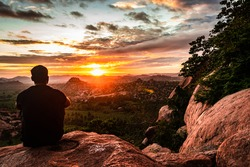 man sitting at mountain top watching sunrise with dramatic sky at morning flat angle shot is taken at Matanga hill hampi karnataka india. the view from here is serene and breathtaking.