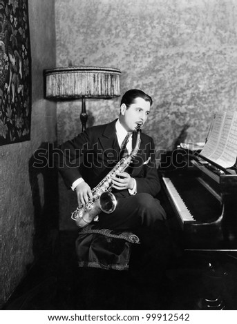 Man sitting at piano playing saxophone