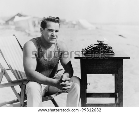 Man sitting at the beach with his typewriter