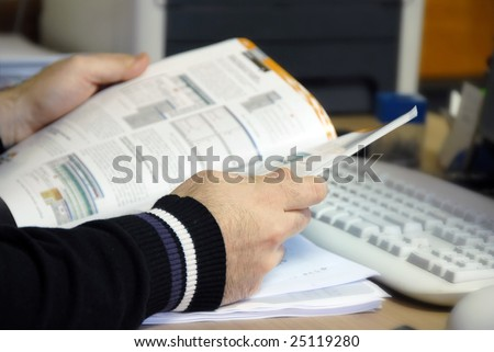 man sitting at the desk in office with magazine in hands