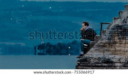 Man sitting at the dock in twilight, thinking about the meaning of life. Lake, headland with church and hills in the background.  Foto stock ©