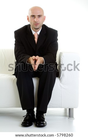 Man sitting at the end of a white couch, wearing a business suit.  Serious expression.  Isolated on white background.