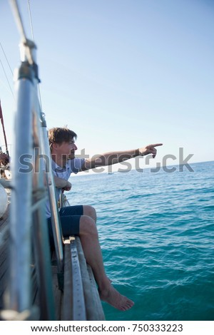man sitting at the rail of a boat #750333223