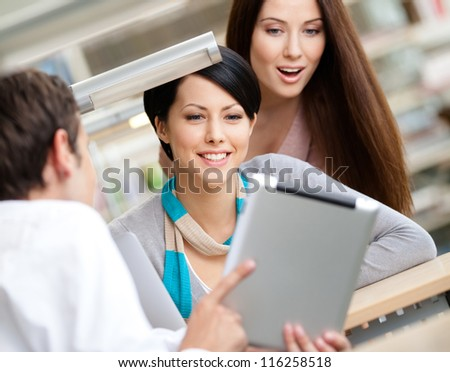 Man sitting at the table at the library shows something interesting in the pad to two women