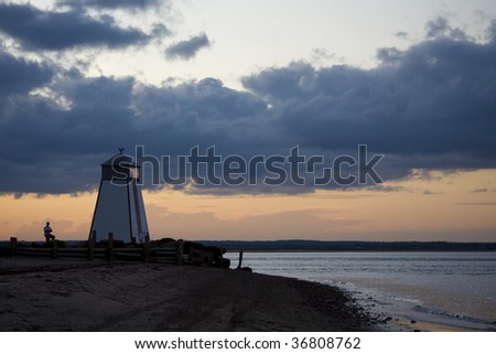 Man sitting by lighthouse enjoying the view
