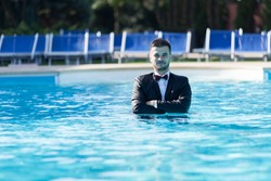 Man sitting by the pool, wearing black suit feeling sad and disappointing.