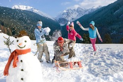 Man sitting down near the sled on a ski slope and being playfully attacked by his family during a snowball fight next to a snowman