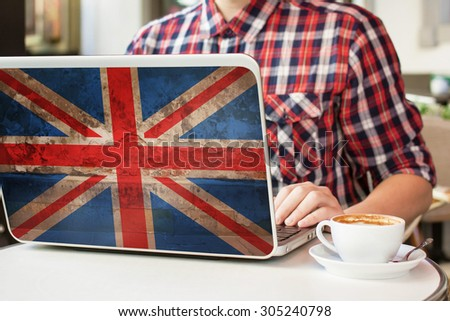 Man sitting in a cafe with cup of coffee and notebook with flag of Great Britain on it. English language learning concept