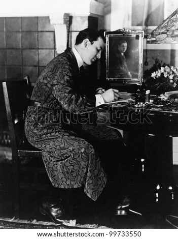 Man sitting in a chair and writing