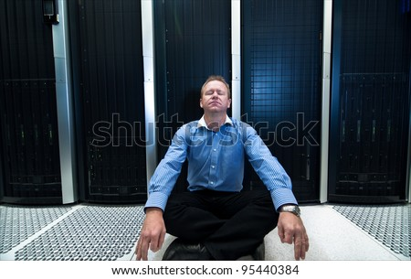 Man sitting in a relaxed meditation posture in front of computer/network data center equipment