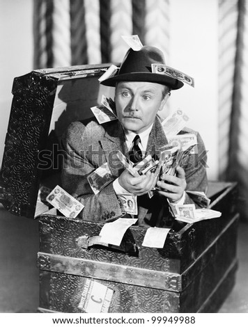 Man sitting in a trunk with money in his hands