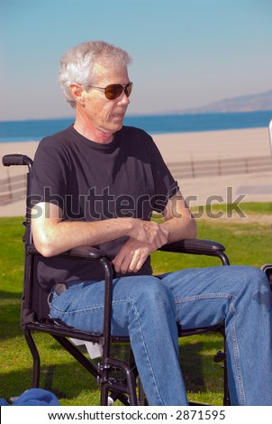 Man sitting in a wheelchair at the beach on a sunny day.