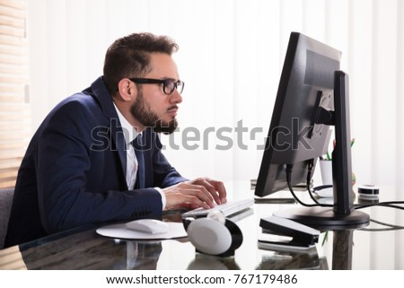 Man Sitting In Bad Posture Working On Computer In Office