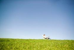 Man sitting in deckchair in field