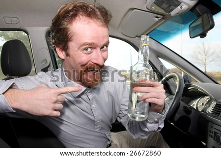 Man sitting in drivers with a bottle alcohol