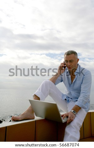 Man sitting in front of a laptop computer on a terrace