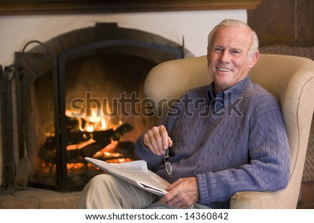 Man sitting in living room by fireplace with newspaper smiling