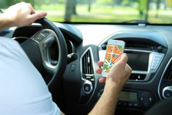 Man sitting in the car and holding smart phone with map gps navigation application