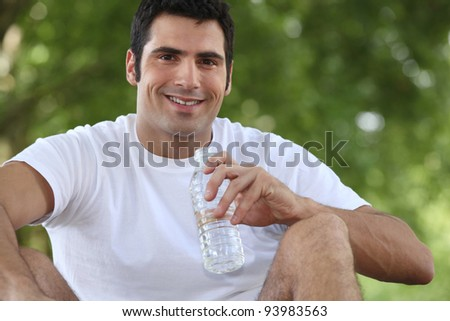man sitting in the park and drinking water