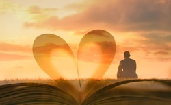 Man sitting looking out to the sunset against heart shape book page.  People, religion, searching for, love, wisdom, and knowledge concept.