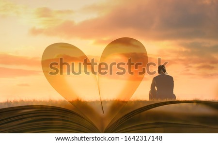 Man sitting looking out to the sunset against heart shape book page.  People, religion, searching for, love, wisdom, and knowledge concept.  Foto stock ©