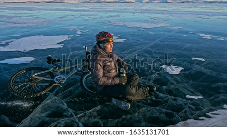 Man sitting near her bike on ice. Athlete cyclist stopped to rest. She sits on the wheel and enjoys the beautiful view of the sunset. The traveler is ride a cycle. Male is riding bike on the ice.