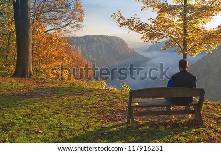 Man Sitting On A Bench Enjoying An Early Morning Sunrise Over A Foggy Genesee River Valley At Letchworth State Park