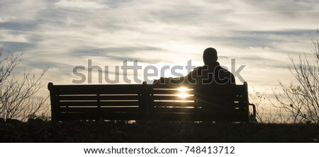 Man sitting on a bench in a park during sunrise. #748413712